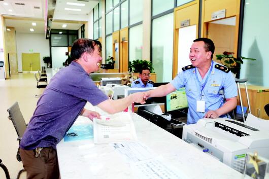 省政府政务服务中心工商窗口首席代表在左脚跟腱手术第二天,拄着拐杖为群众服务