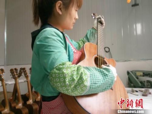 工人在调音房对吉他调音。 周燕玲 摄