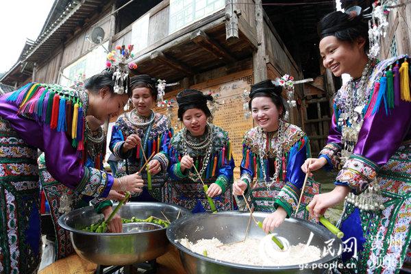 贵州省榕江县乌公侗寨的侗族姑娘将糯米装入竹笋,准备蒸煮竹米饭。