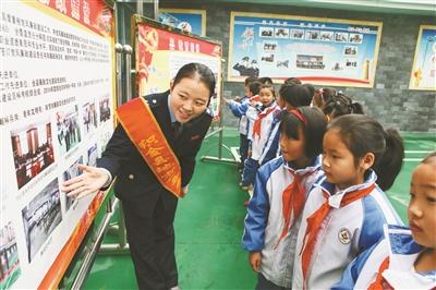 图为织金县地税局税收普法宣传员为小学生讲解税法知识.